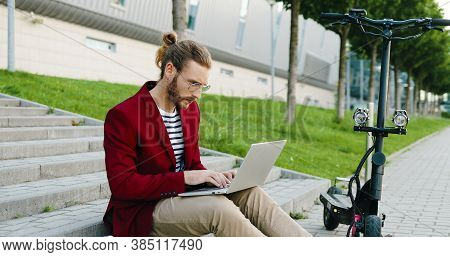 Young Caucasian Handsome Man In Glasses And Red Jacket Sitting On Steps Outdoors, Working On Laptop