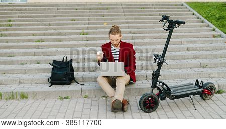 Young Caucasian Handsome Man In Red Jacket Sitting On Steps Outdoors, Working On Laptop Computer, Si