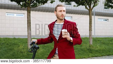Caucasian Young Handsome Man In Red Jacket Standing On Street At Bike Or Electric Scooter And Drinki