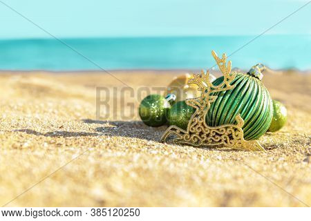Christmas Decoration Green Balls And Gold Reindeer On The Tropical Beach Near Ocean, A Summer Christ