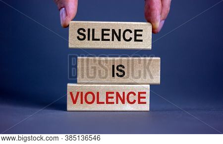 Male Hand Placing A Block With Word 'silence' On Top Of A Blocks Tower With Words 'silence Is Violen