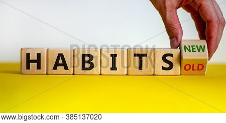 Male Hand Turning A Cube And Changes The Expression 'old Habits' To 'new Habits'. Beautiful Yellow T