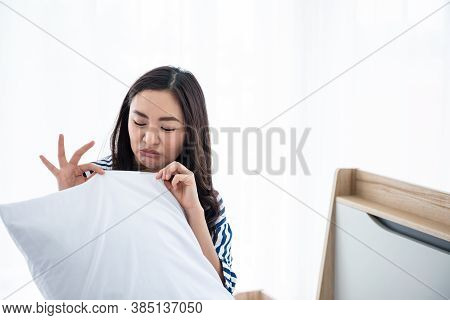 An Asian Woman Sniffing A White Pillow, Which Smelled Smelly And Damp. And Showing Disgusting Facial