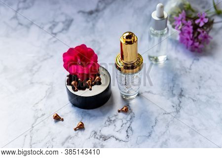 Glass Bottle With Dropper, Moisturizing And Healing Skin Serum With Vitamin C On A Marble Background