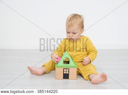 Adorable Happy Toddler Boy Sits At The Floor And Play With A Toy Sorter.