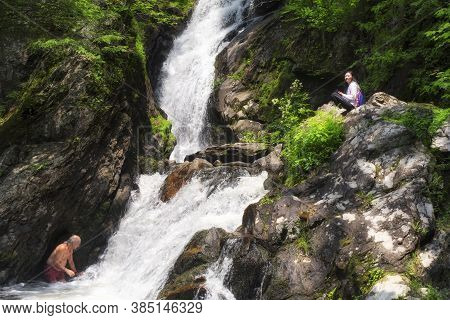 Sheffield, Massachusetts. June 22. 2019. A Man Swimming At The Base Of Campbell Falls While A Chines