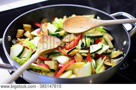 Stir Fry Fresh Chopped Eggplant, Zucchini And Peppers In The Pan With Wooden Spoon. Preparing Health