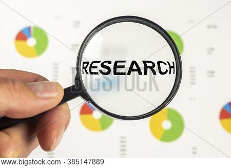 Research Concept, Word Research In Magnifying Glass Loupe On White Documents With Charts Diagrams, G