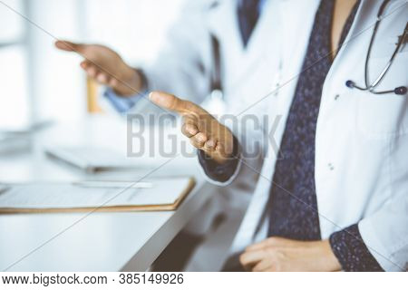 Two Doctors Sitting And Offering Helping Hand For Shaking Hand Or Saving Life. Medical Help, Counter