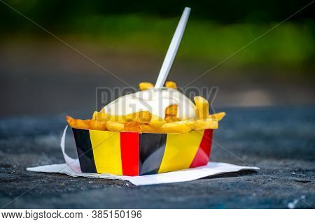 Paper Box In Colors Of Belgian Flag With Fried Potato Frit Chips And Mayonnaise Sauсe.