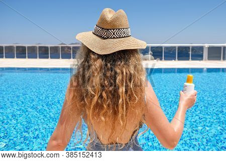Young Woman In Straw Hat Holding Sun Protection Cream Suntan Sunscreen Lotion Near Swimming Pool At