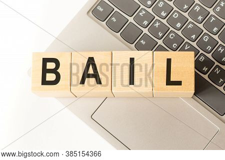 Word Bail. Wooden Cubes With Letters Isolated On A Laptop Keyboard. Business Concept Image.