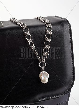 Women`s Silver Necklace With Baroque Pearl Pendant On Male Black Leather Briefcase. Close-up Shot