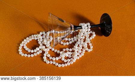 Natural White Pearl Beads On A Yellow Background And An Empty Martini Glass. On The Table Is An Inve