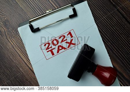 Red Handle Rubber Stamper And 2021 Tax Text Isolated On The Table.