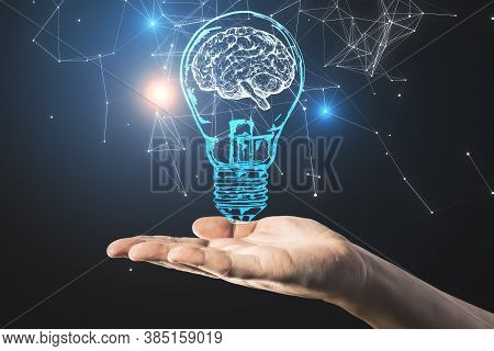 Hand Holding Light Bulb With Brain Hologram. Idea And Brainstorm Concept. Close Up