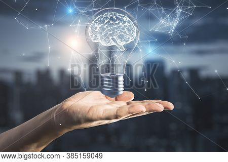 Hand Holding Creative Lamp With Brain Hologram On Night City Background. Success And Startup Concept