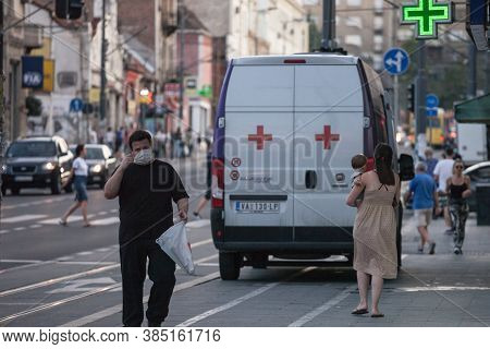 Belgrade, Serbia - August 20, 2020: Middle Aged Man Walking And Touching To Adjust His Face Mask Pro