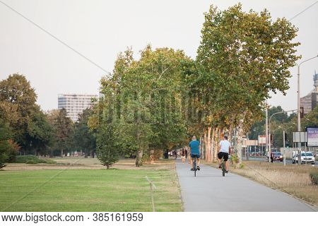 Belgrade, Serbia - August 21, 2018: Two Cyclists On Their Bicycles Driving Through A Park On A Bike