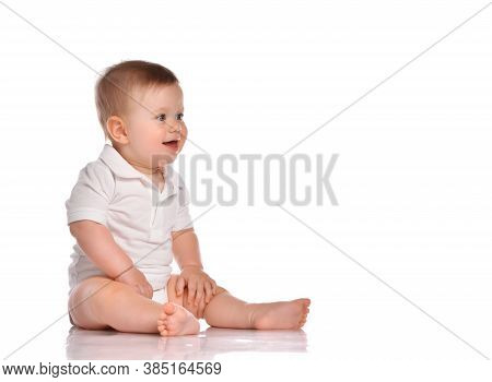 Cute Little Boy In White Overalls, Baby Toddler Sitting And Happy Looking At The Corner, Isolated On