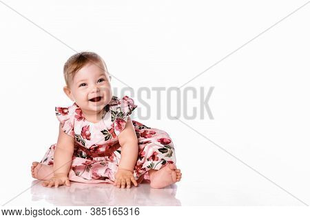 Cute Little Girl In A Beautiful Princess Dress Sitting On The Floor On A White Studio Background. Cl