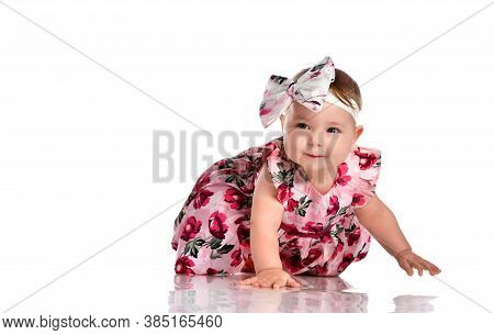 Beautiful Baby Girl Wearing Colorful Dress And Headband Bow Crawling On Floor. Pretty Cute Female To