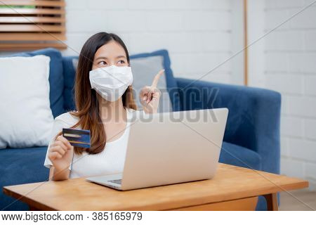 Young Asian Woman In Face Mask Holding Credit Card Shopping Online With Laptop Computer Buy And Paym