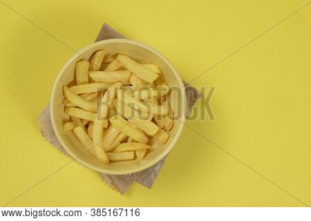 Portion Of Potato Fries In Ceramic Bowl On Isolated Yellow Background