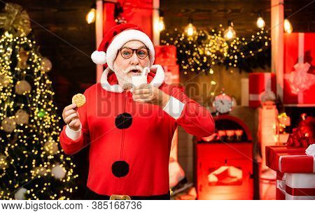 Happy Santa Claus Eating A Cookie And Drinking Glass Of Milk At Home Christmas Interior. Santa Make