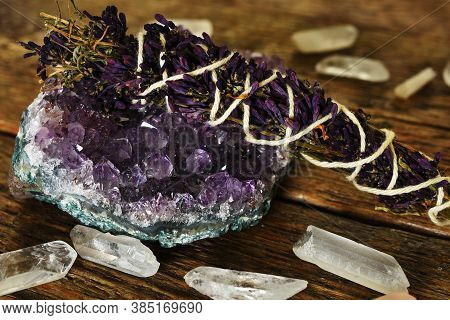 A Close Up Image Of An Amethyst Geode And Lilac Smudge Stick With Clear Quartz Crystals On A Dark Wo