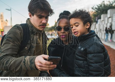 Portrait Of Lovely Mixed Race Ethnic Family Having Fun, Relaxing And Using Mobile Phone At The Park