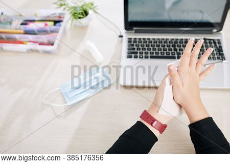 Businesswoman Wiping Hands With Antibacterian Desinfecting Wipes Over Office Desk With Laptop And Me