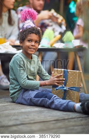 afro-american boy sitting on wooden floor with present between legs with other guests in the background at birthday party