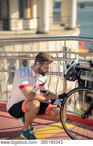 Cyclist Crouched Near Wheel Of His Bike