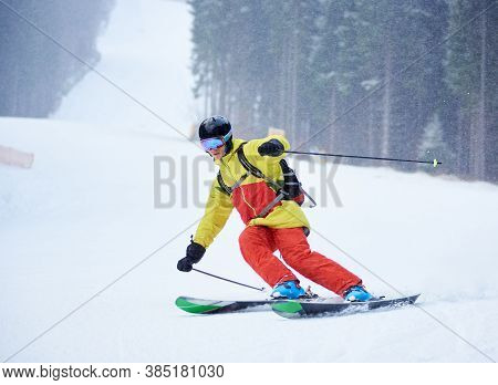 Front View Of Young Male Skier Downhill Skiing And Doing Carve Turn On High Snowy Slope. Skiing Duri
