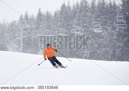 Adult Proficient Man Skiing On Ski Run Slope During Heavy Snowfall. Chairlift And Fir Forest On Back