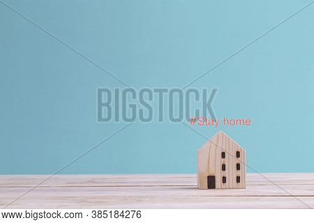 Covid-19 Coronavirus Stay At Home Concept , Mini Wooden Home With Text Hashtag #stay Home On The Blu
