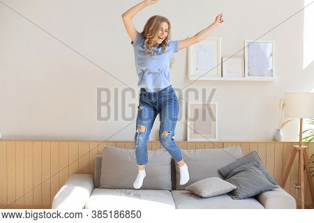 Attractive Young Woman Is Having Fun At Home. Girl Is Jumping And Dancing On Sofa.