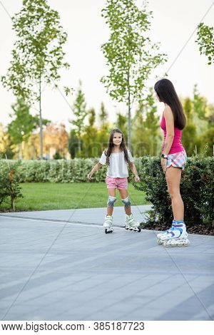 Young Mother And Little Daughter Rollerskating In Park. Girls Having Fun Outdoor
