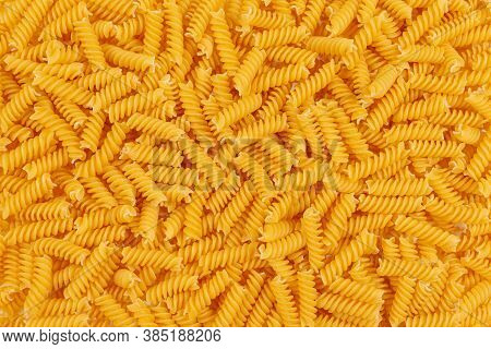 Uncooked Fusilli Pasta Background. Close Up Of Raw Fusilli Pasta. Top View