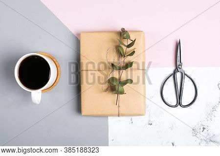 Tri-color Ackground With Cup Of Coffee, Gift Present With Decor Eucalyptus. Flat Lay, Top View.