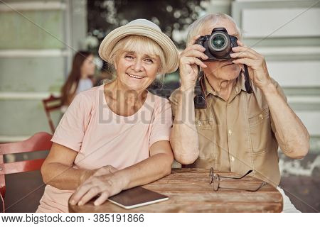Two Modern Pensioners In An Outdoor Cafe