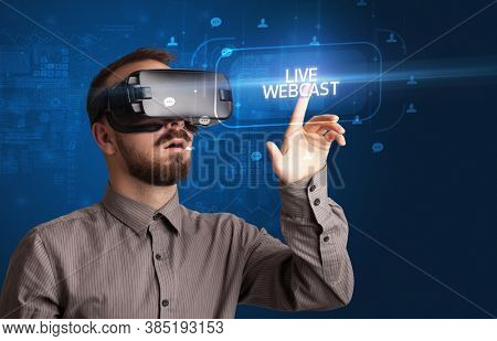 Businessman looking through Virtual Reality glasses with LIVE WEBCAST inscription, social networking concept