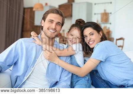 Positive Friendly Young Parents With Smiling Little Daughter Sitting On Sofa Together While Relaxing
