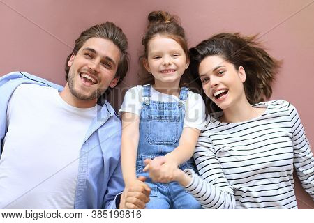 Top View Portrait Of Smiling Young Parents With Little Preschooler Daughter Lying Relaxing On Warm F