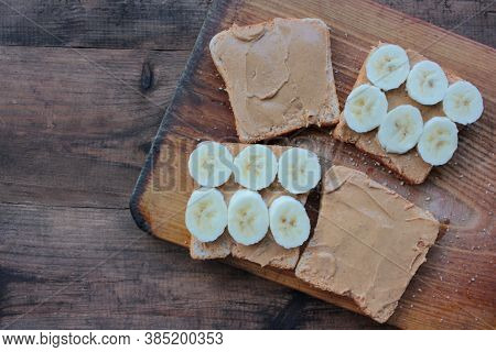 Close-up Of Peanut Butter Banana Sandwiches On Wooden Background. Slices Of Whole Wheat Bran Bread W