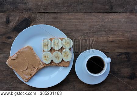 Cup Of Coffee And Peanut Butter Banana Toast On Wooden Background. Slices Of Whole Wheat Bran Bread