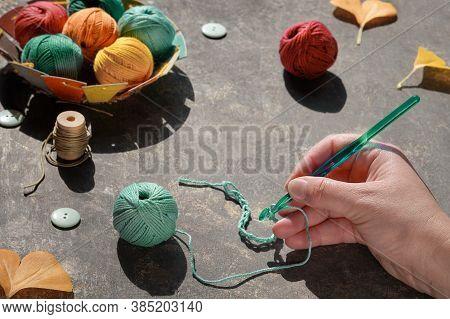 Hand With Crochet Hook With Thread, Yarn Balls, Buttons, Felt Pumpkins, Fall Leaves. Autumn Arrangem