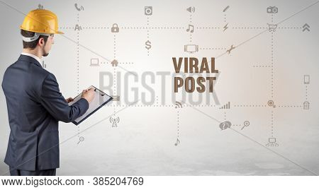 Engineer working on a new social media platform with VIRAL POST inscription concept