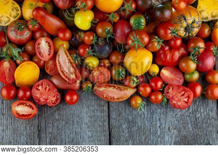 Tomatoes Of Different Varieties And Colors Top View. Layout On A Wooden Background. Food. Sliced Tom